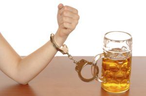 Hand Handcuffed to a beer
