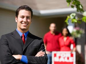 Man Outside of House with for sale sign