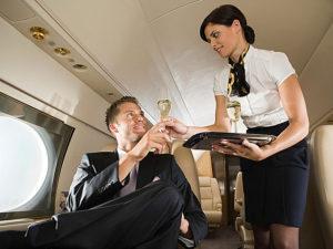 Flight attendant serving champagne on plane