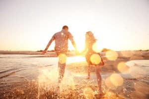Couple splashing through ocean on the beach