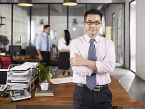 Man with arms crossed leaning against desk
